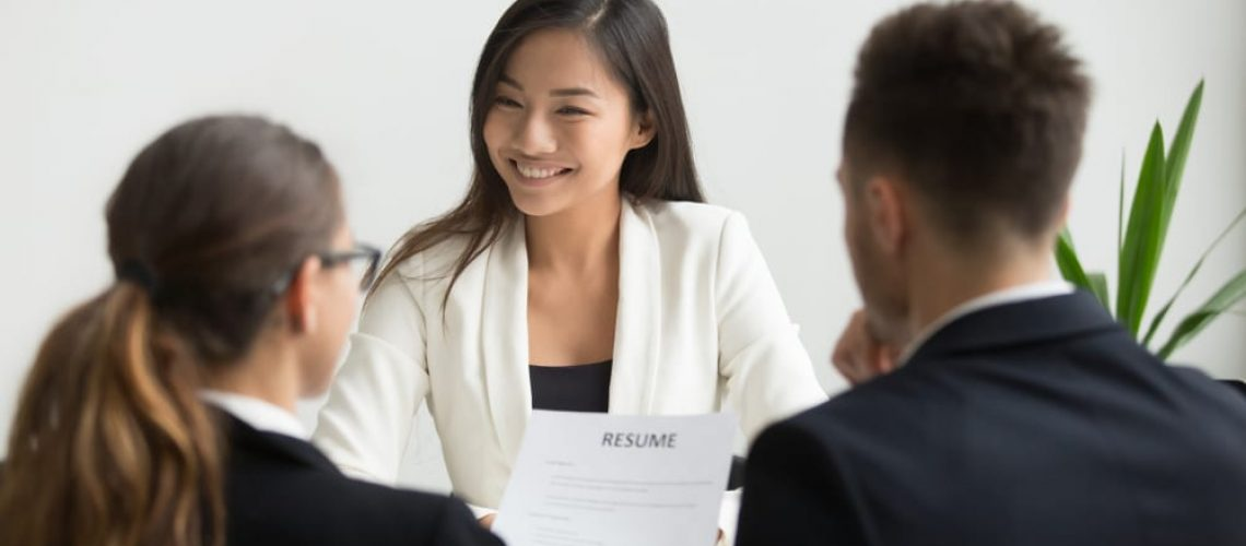 happy smiling woman in white top sits before two people in dark business suits during hiring process making a choice for hire